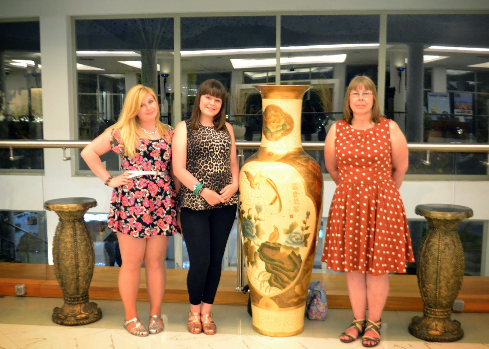 myself, my sister, and my mom standing in the hotel reception with a large ornate vase in between us