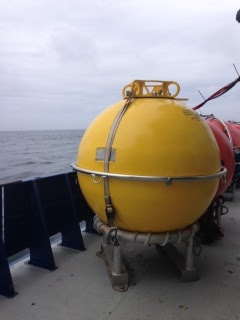 A human-height, spherical, yellow mooring sits on deck the Neil Armstrong boat. The mooring is at the center, with the ocean in the background.