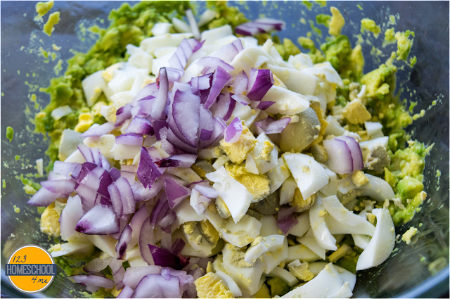 mix together red onion, smashed avocado, and chopped hard boiled eggs