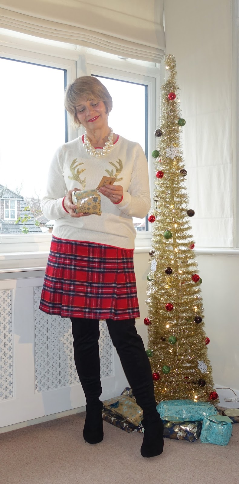 Image showing an over 50s fashion blogger by a Christmas tree in a Christmas jumper and red tartan skirt