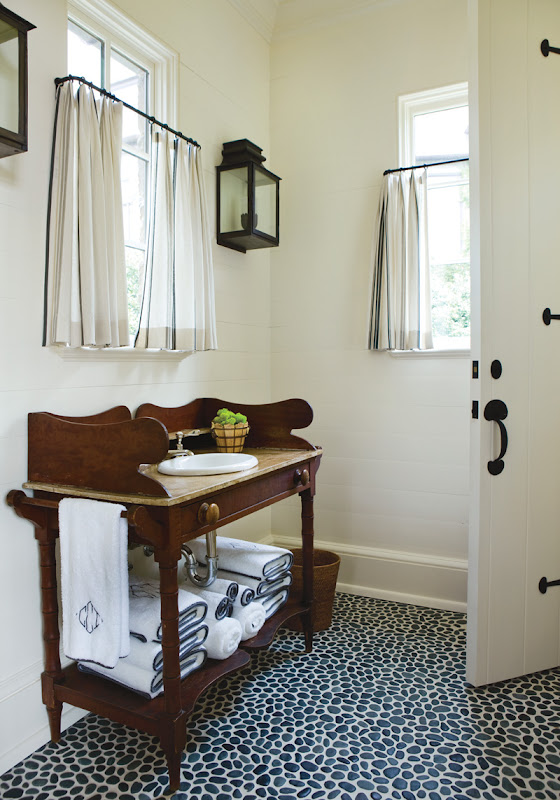Bathroom with pebble floor, wall mounted lantern and a console sinks made of wood and marble