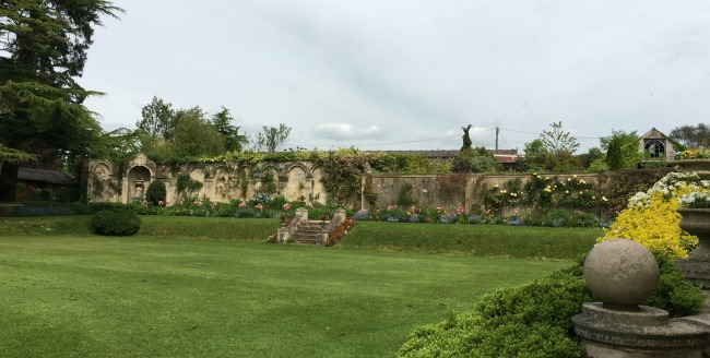 view across lawn at wall and flower beds