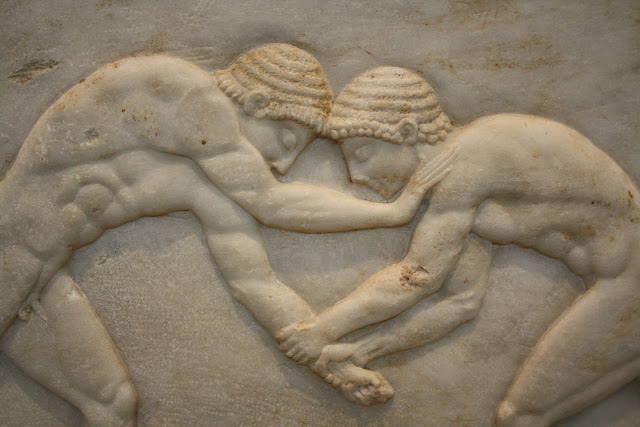 Ancient Greek Olympic wrestlers, a relief from a funerary kouros base. National Archeological Museum Athens.