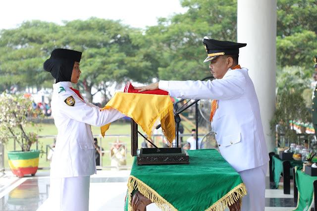 Bupati Asahan Taufan Gama Simatupang menyerahkan Bendera Merah Putih kepada anggota Paskibra untuk dikibarkan.