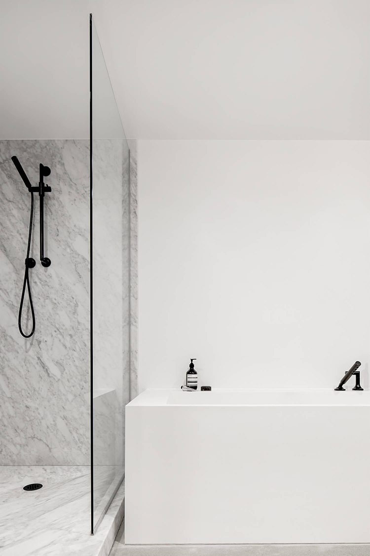 Minimalistic bathroom with marble shower by Atelier Barda