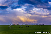 Cramer Imaging's professional quality landscape photograph of a farm field and equipment with colorful clouds in Rexburg, Madison, Idaho