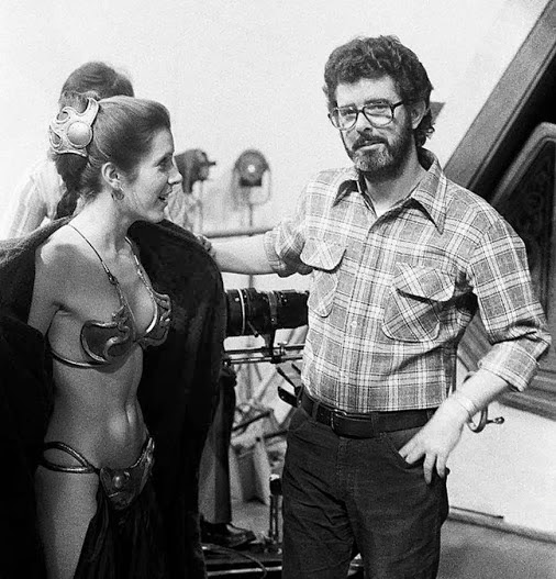 Carrie Fisher flashing George Lucas while wearing one of the most famous bikini costumes ever