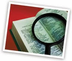 photo of an open book of definitions with a magnifying glass on top
