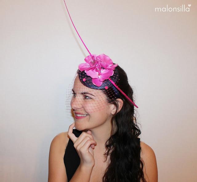 Chica con tocado tipo casquete pequeño con orquideas fucsias, pluma raquis fucsia y velo.
