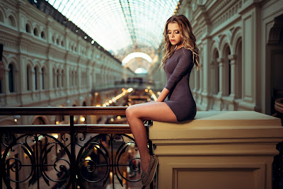 Linda chica sentada encima de un pilar