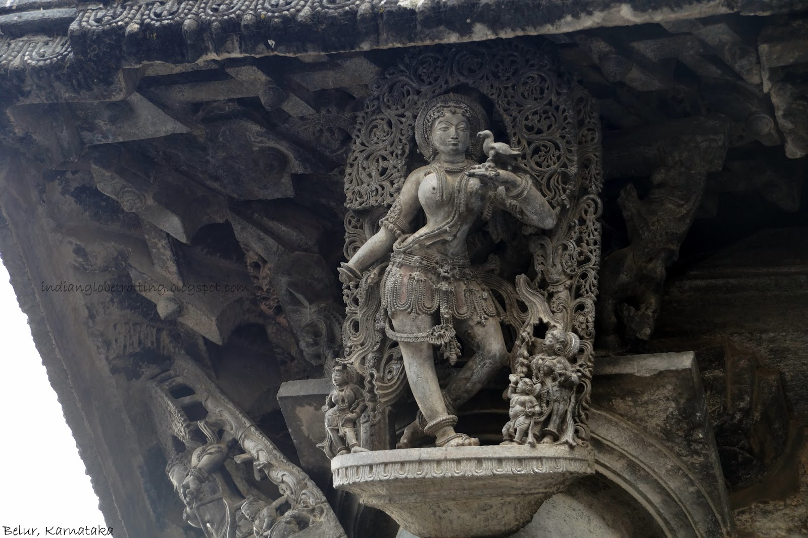 the sculpture of lady with parrot in belur