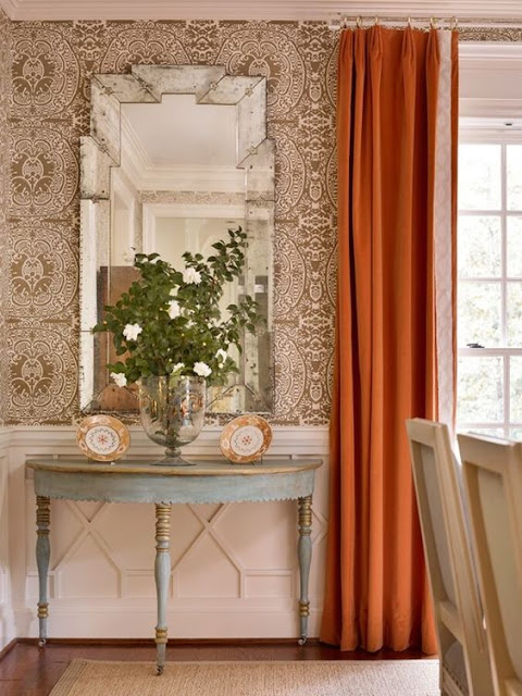 Pumpkin curtains and elegant blue demilune table in beautiful room