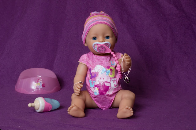 A BABY born doll reaching out her hand with her friendship bracelet, sitting next to her water bottle and potty