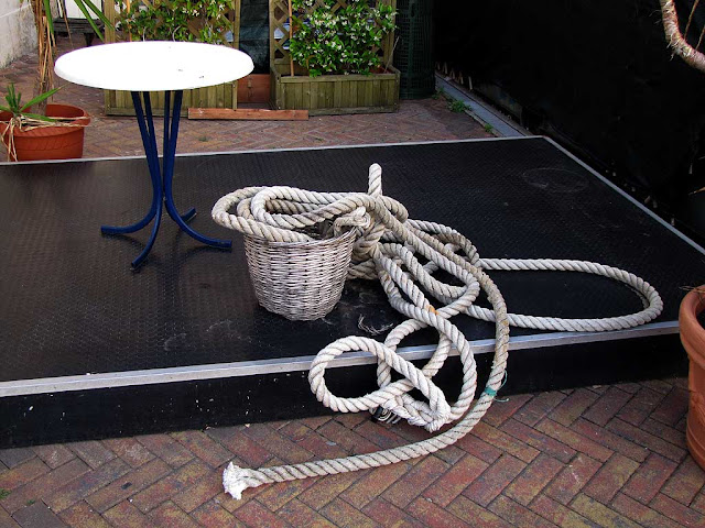 Table and basket with a coil of rope outside a bar, Porto Mediceo, Livorno