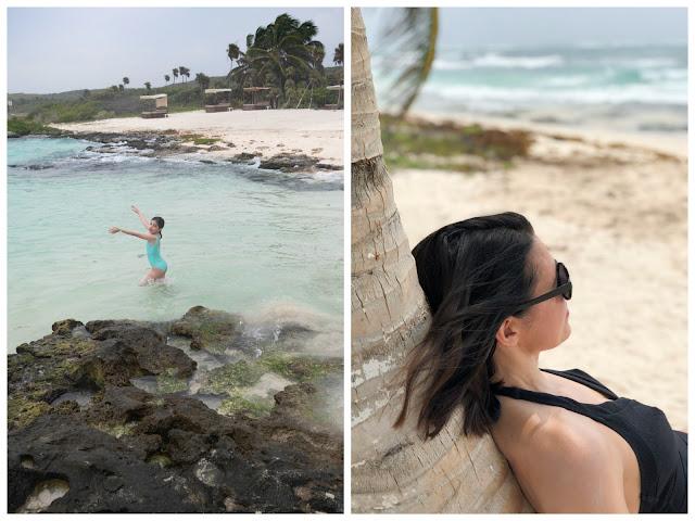Niña en una piscina natural junto al mar y mujer tomando el sol apoyada en una palmera