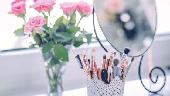 Imagem ilustrativa ao tema: bancada com flores, espelho e pinceis de maquilhagem