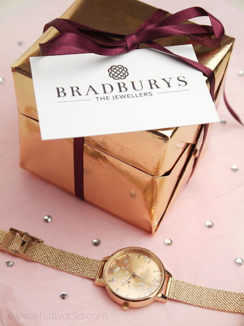 a rose gold olivia burton watch and a rose gold cube with a bradburys the jewellers business card tucked in the wrapping sit on pink tissue paper