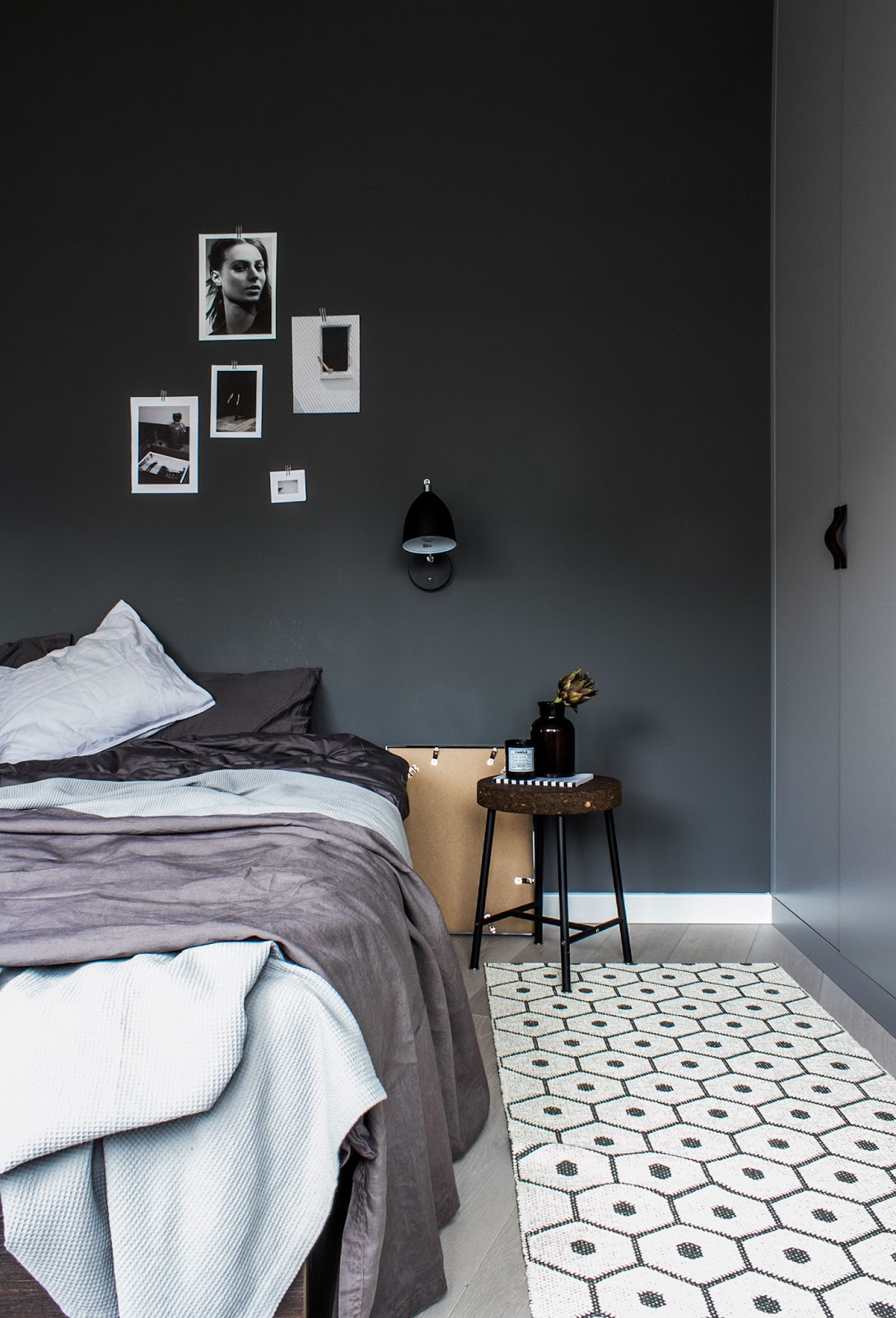 inside of a nordic bedroom, black painted walls, pattern rugs