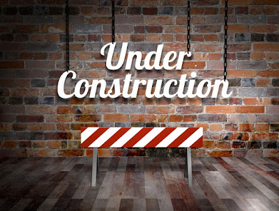 "A big sign on a brick wall says, ""Under Construction"""