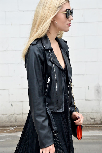 Profile view of cat-eye glasses in a all black fall outfit