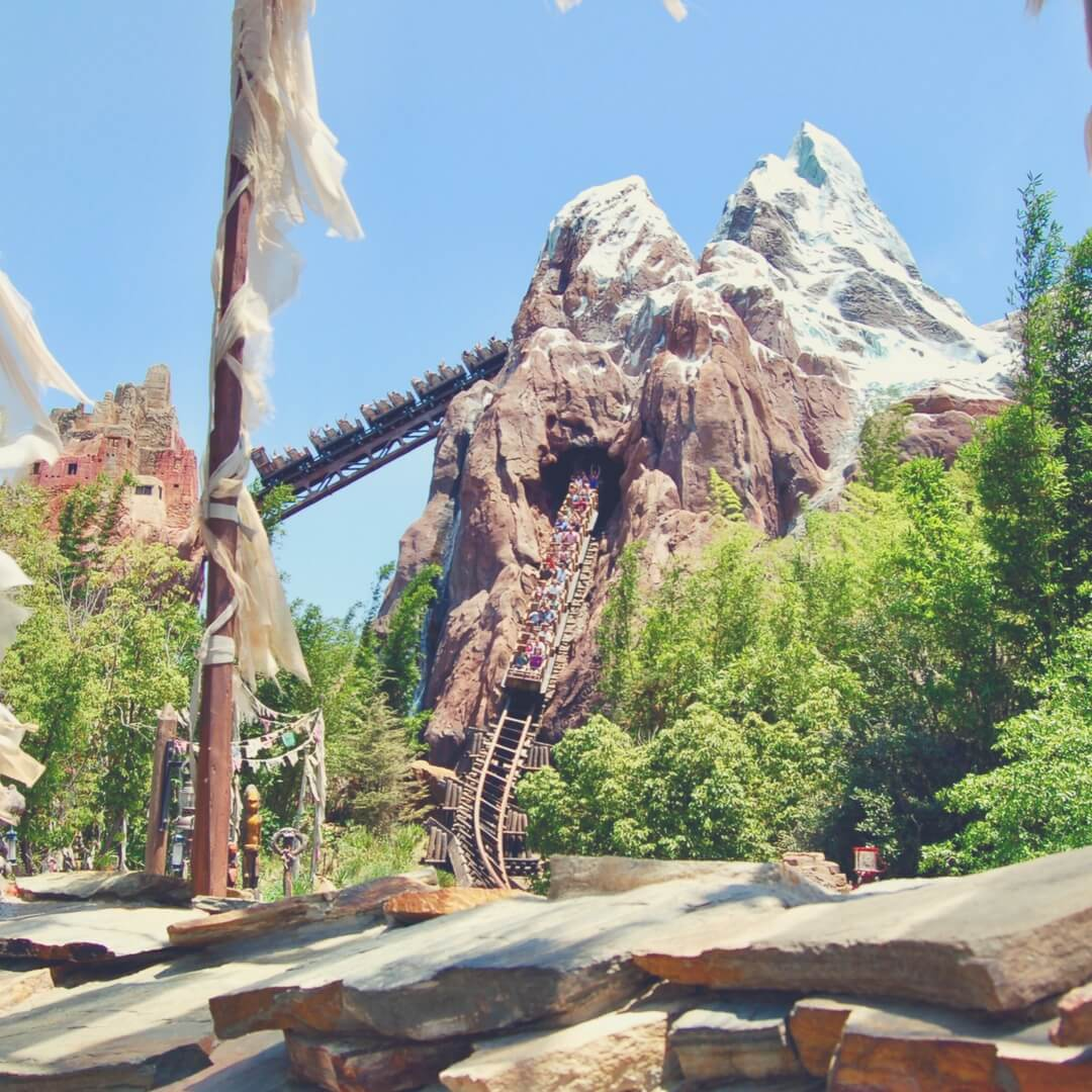 Expedition Everest in Animal Kingdom, Walt Disney World, Orlando. One train is going up the track towards the large mountain, another train is coming out of the front of the mountain. The sun is shining.
