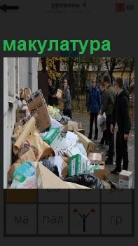 Около здания школьники складывают макулатуру, которую принесли и сдают