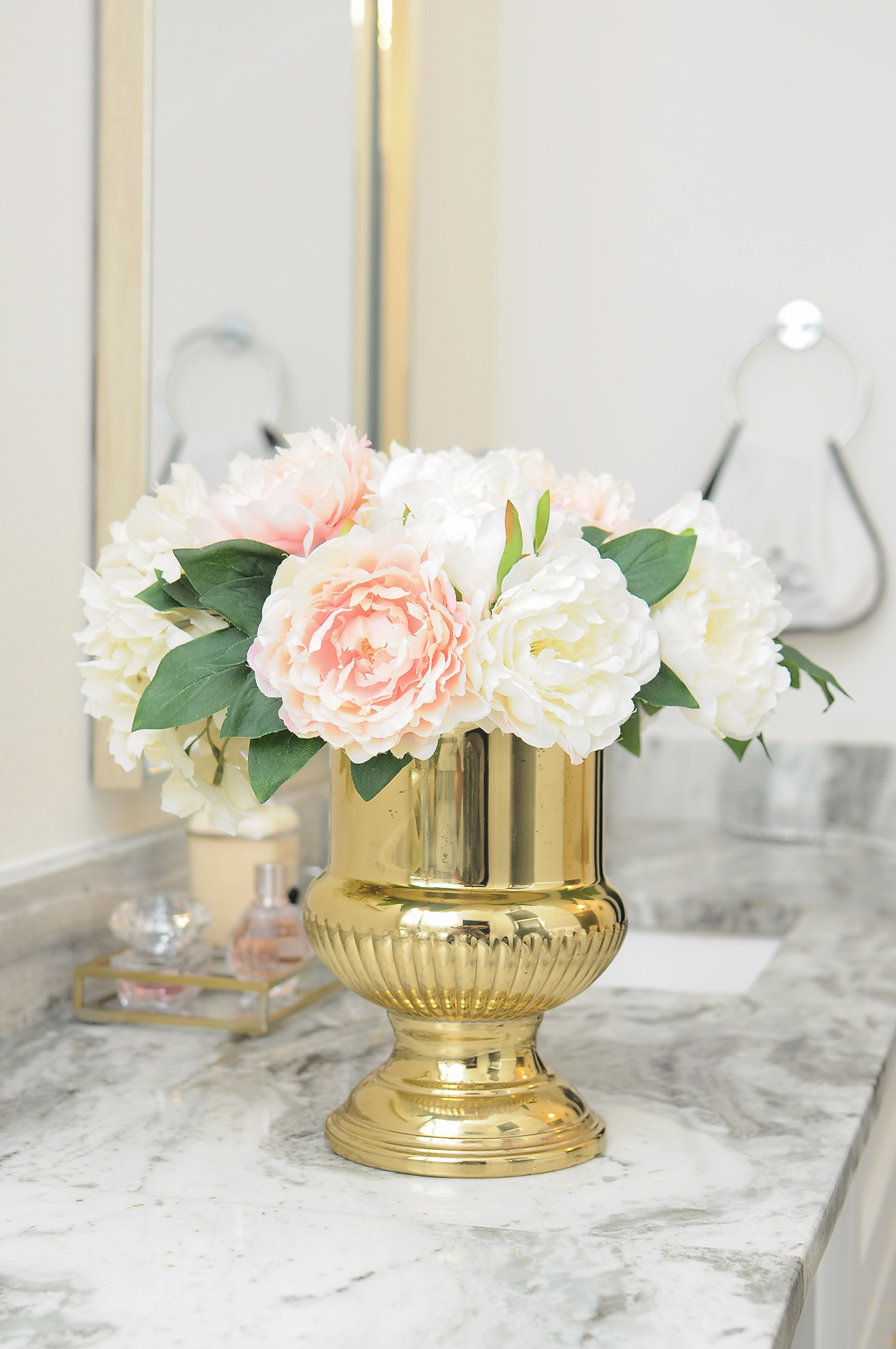 Faux peonies look beautiful and add a dash of glam when paired with a vintage brass urn in this master bathroom suite.