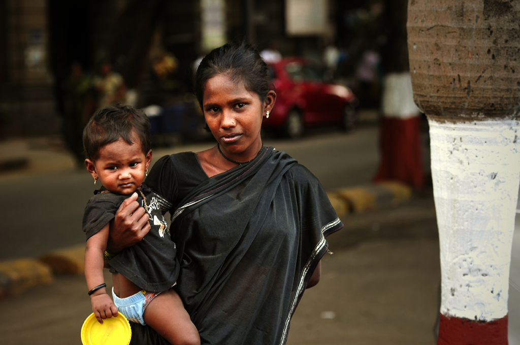 Portrait photo of a begging mother with a baby in her arms in Mumbai in India.