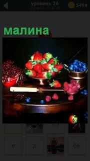 На круглом столе стоит ваза с клубникой, другая с черникой и малина на столе, красная смородина