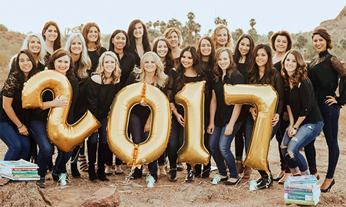 Group photos of a graduating class holding balloons that read 2017, standing in a desert landscape.  their are college books around them.