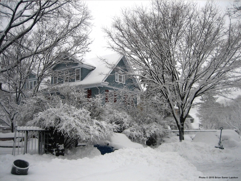A big old house surrounded by tall, bare trees in wide shot, all blanketed in fresh white snow, mounds of which are curbside in foreground although you can't see the curb