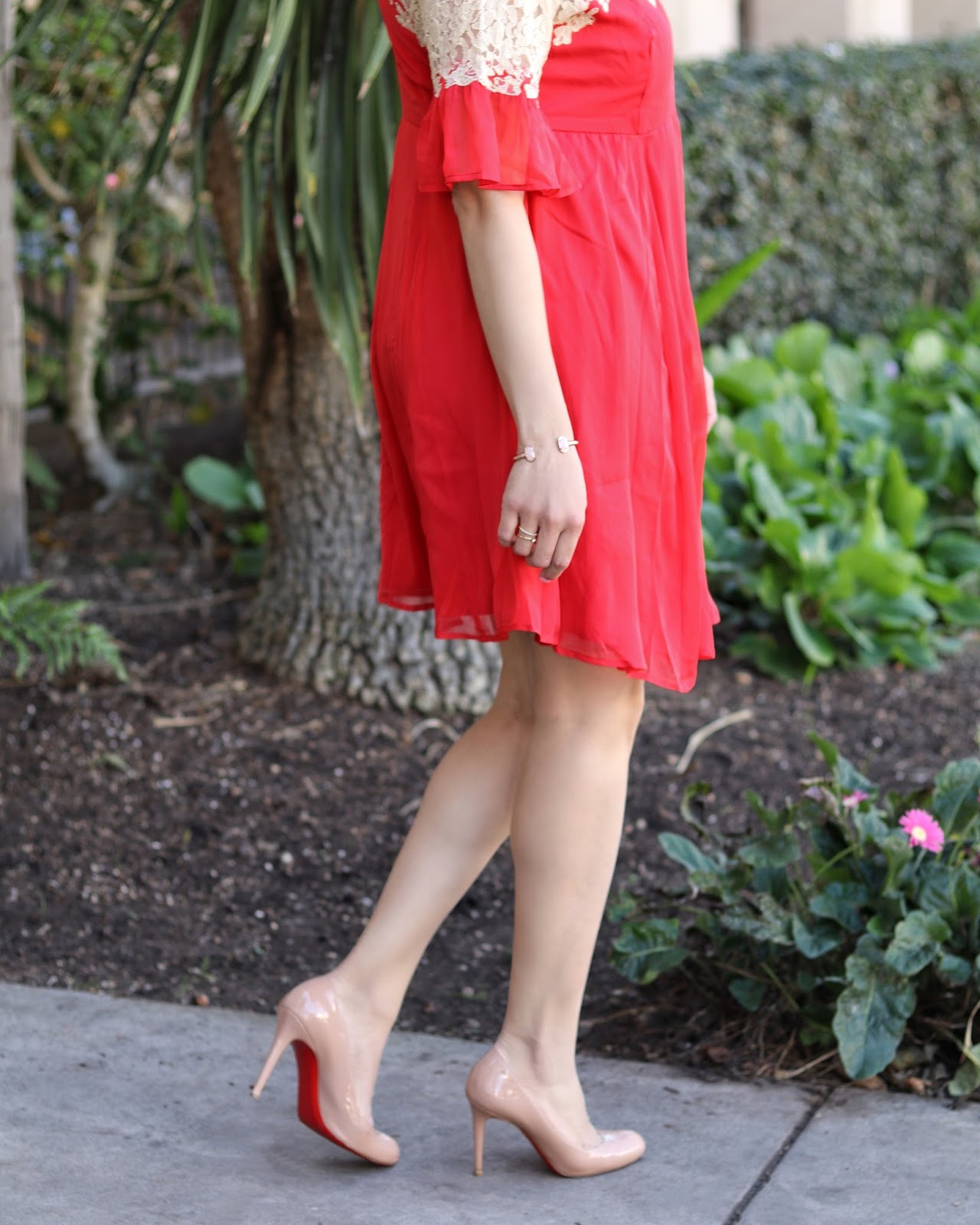 Nude patent leather Christian Louboutin, kendra scott rose gold bracelet, flowy red dress