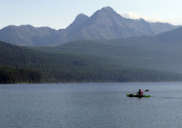 Kayaker with view of Rocky Mountains (Credit: AP Photo/Matt Volz) Click to Enlarge.