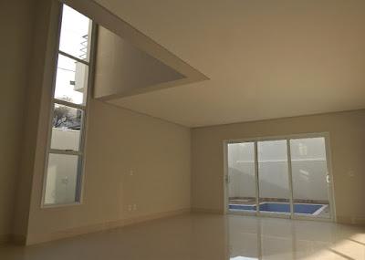 As salas de estar e jantar possuem ampla área de esquadrias que garantem a iluminação natural durante o dia. O pé-direito duplo é acompanhado por extensas janelas seteiras que integram o ambiente ao mezanino.