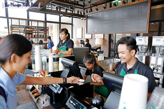 A barista serves customers at the grand opening of the new Starbucks outlet outside Aeon Mall in Phnom Penh. Pha Lina