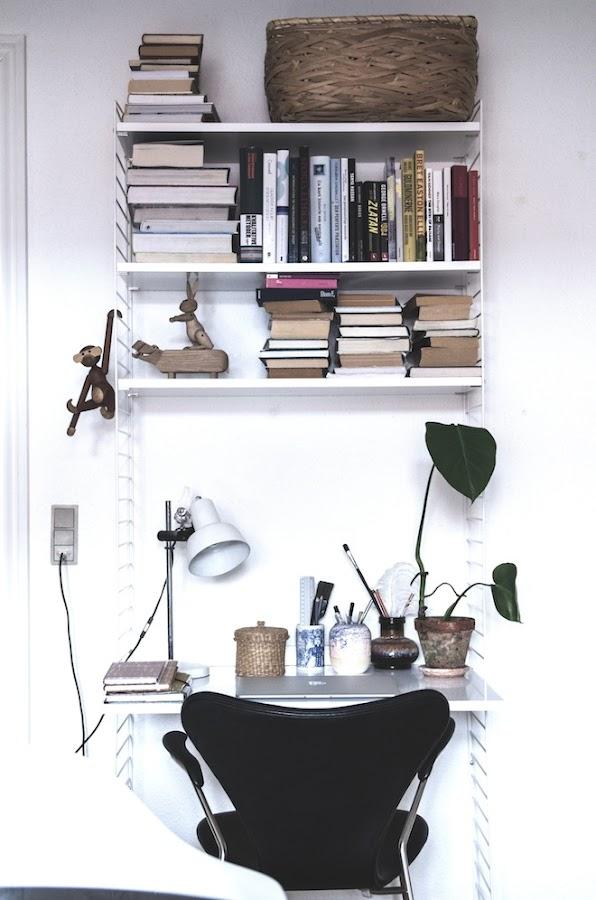 zona de estudio pequeña pero práctica con estantería volada con libros, plantas, foco pinza