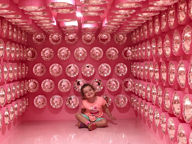 Toddler girl sitting and smiling in a pink room with chrome objects pasted to the walls and short ceiling