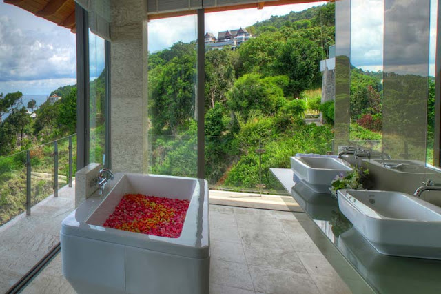 Modern corner bathroom with ocean and vegetation view