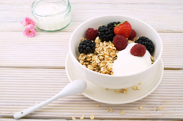 White bowl with oats, berries and yoghurt on white wooden table