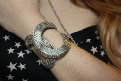 a close up of a silver overlapping cuff being worn by francesca sophia