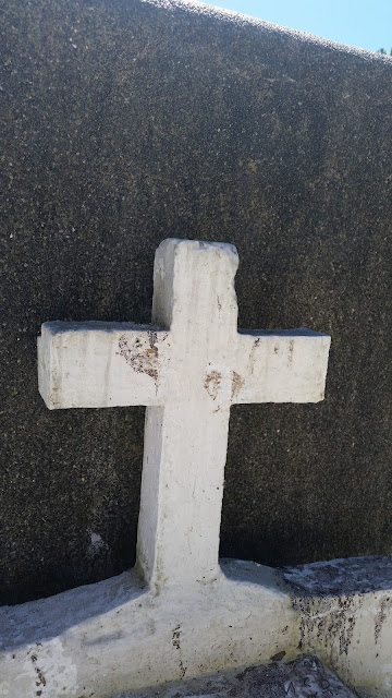 Freshly painted cross with white color in a grave