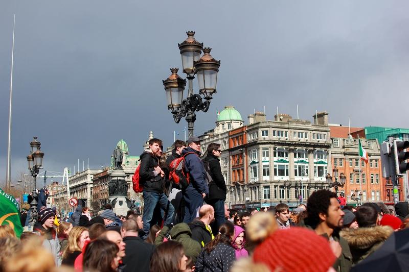 plusieurs personnes accrochées à un lampadaire pour apercevoir la parade de l'indépendance du pays