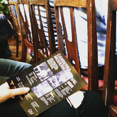 Person holding a flier for the Canberra Modern festival while seated behind a row of chairs designed by Fred Ward.