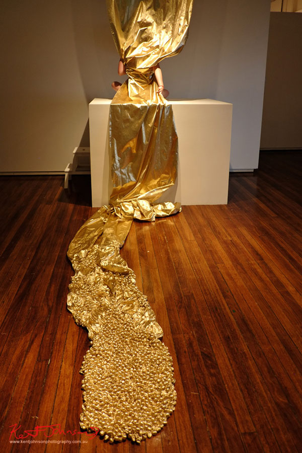 Gold fabric wraps the performer, COLLUSIVE MISCELLANY by Amy Claire Mills, Bailee Lobb. Photographed by Kent Johnson for Street Fashion Sydney.