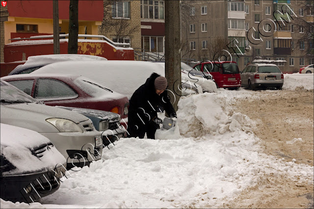 Минск. Беларусь. Старуха складывает снег в полиэтиленовый пакет
