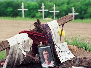 A photo of David Koresh rests beside a wooden cross as part of a monument erected in Waco, Texas, by supporters of the Branch Davidian leader and founder, Friday, April 30, 1993. (AP Photo/NewsBase) Read more: https://www.smithsonianmag.com/history/true-story-waco-still-one-contention-180968002/#Y7OBbhH61PI6iXuX.99 Give the gift of Smithsonian magazine for only $12! http://bit.ly/1cGUiGv Follow us: @SmithsonianMag on Twitter