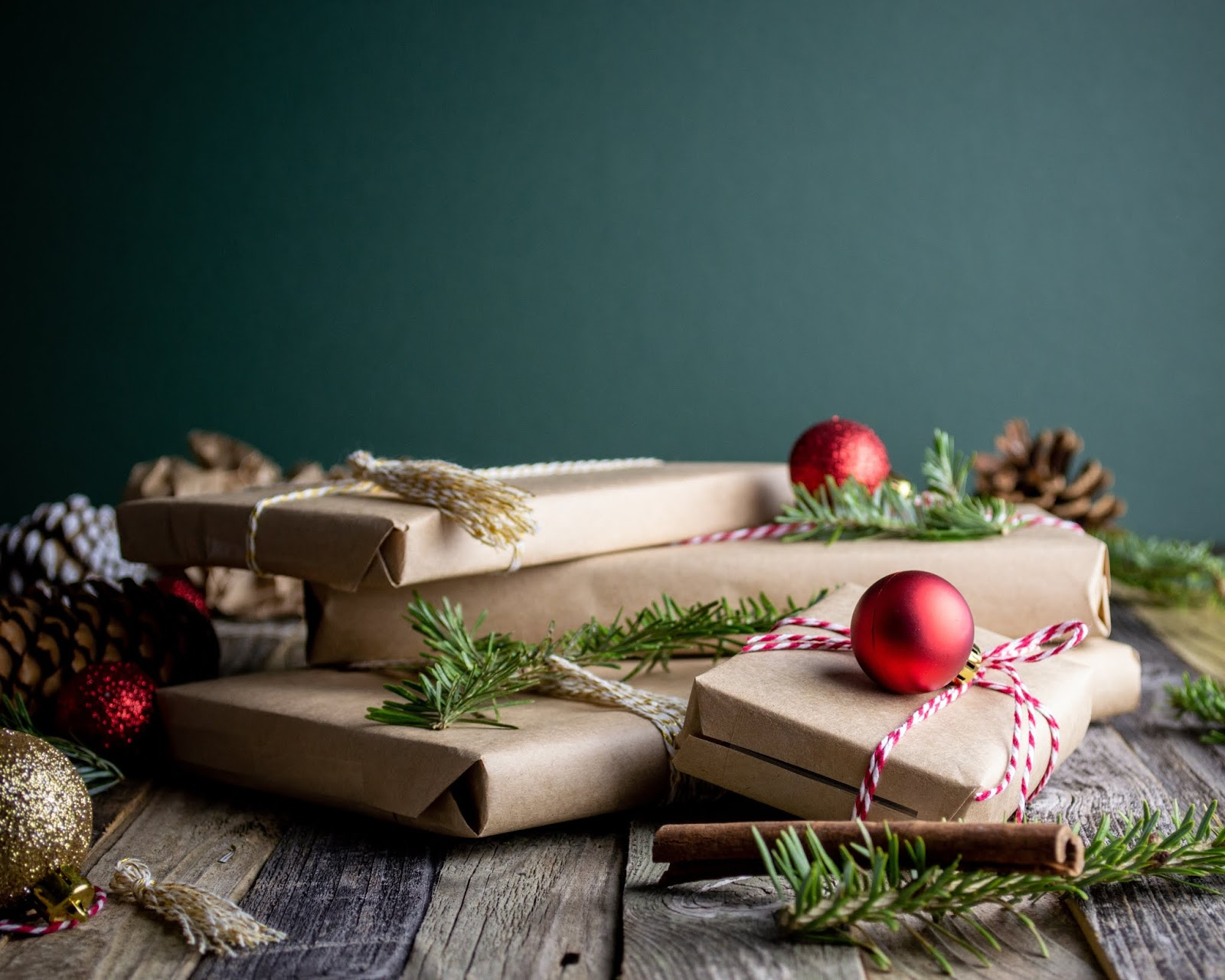 Four presents wrapped in brown paper with red and white ribbon string around them, in front of a teal background, surrounded by sprigs of pine, baubles, and cinnamon sticks.