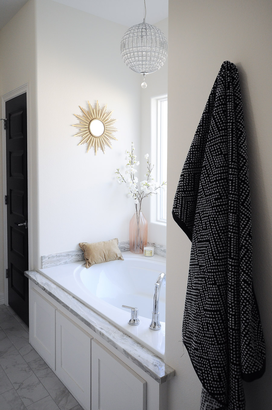 Jetted bathtub looks like a relaxing retreat when paired with gold and blush pink accents in a master bathroom suite.