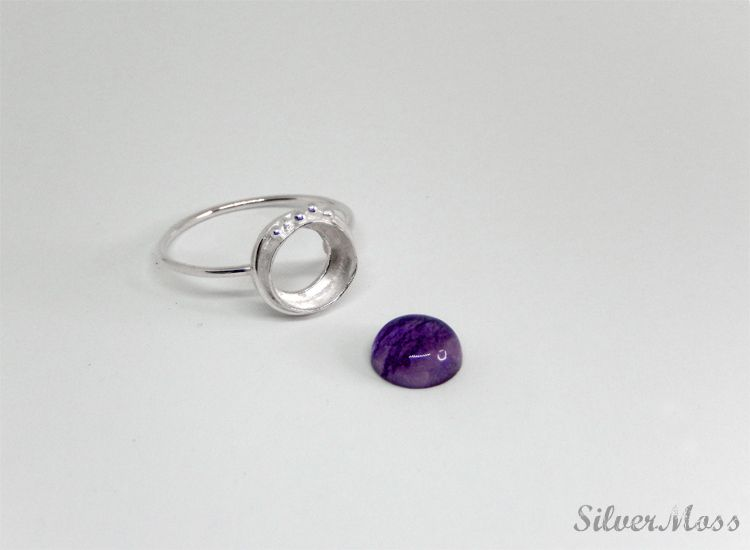 purple fluorite gemstone cabochon next to a handcrafted sterling silver ring setting
