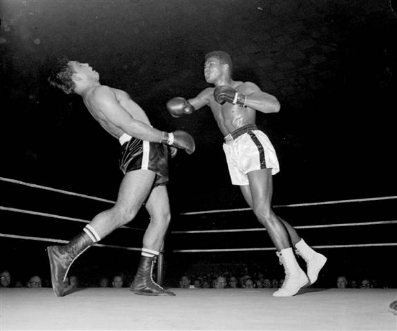 Muhammad Ali, right, attacks Alex Mitoff in the sixth round in which Ali clobbered the Argentinean to the canvas, on Oct. 7, 1961 in Louisville, Ky. H.B. Littell / AP, file